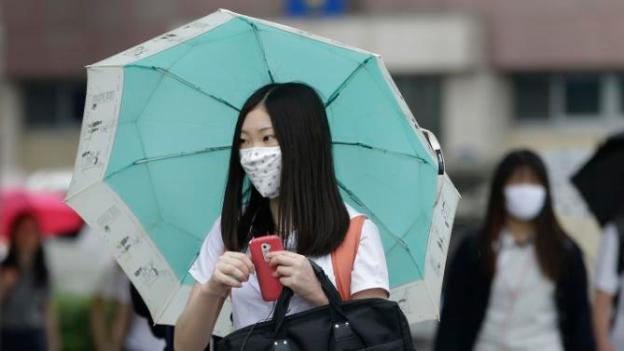 """A South Korean high school student wears a mask as a precaution against the MERS, Middle East Respiratory Syndrome, virus as she goes to school in Seoul, South Korea, Friday, June 5, 2015. Sales of surgical masks surge amid fears of the deadly, poorly understood virus. Airlines announce """"intensified sanitizing operations."""" More than 1,100 schools close and 1,600 people - and 17 camels in zoos - are quarantined. The current frenzy in South Korea over MERS brings to mind the other menacing diseases to hit Asia over the last decade - SARS, which killed hundreds, and bird flu. (AP Photo/Ahn Young-joon)"""